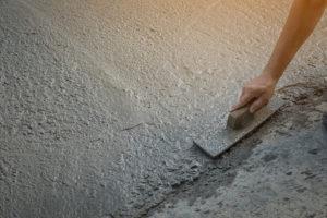 Construction workers leveling concrete pavement
